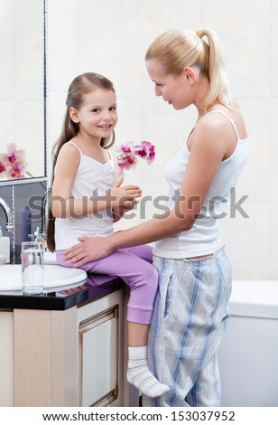 Mother and daughter talk about something in bathroom - stock photo