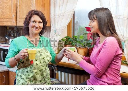 Mother and daughter talking, drinking tea in kitchen - stock photo