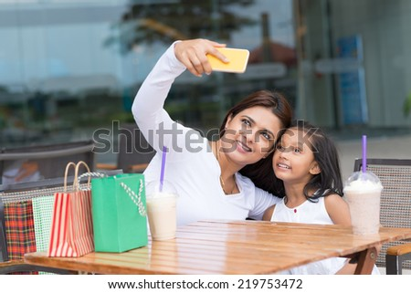 Mother and daughter talking selfie after shopping - stock photo
