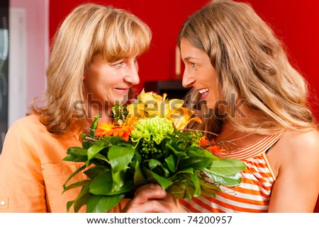 Mother and daughter � the daughter has given her mother flowers - stock photo