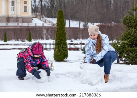 Mother and daughter together making snowman with snow in winter park - stock photo