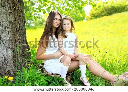 Mother and daughter together on the grass near tree in summer day, mom with child outdoors - stock photo