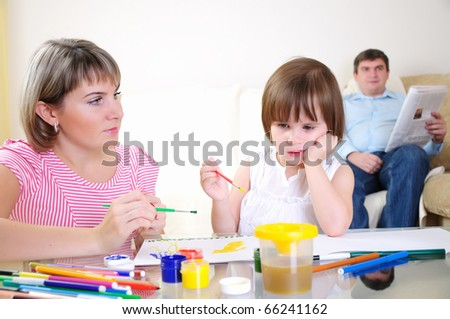 Mother and daughter together paint an album and have fun together. - stock photo