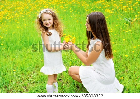 Mother and daughter together with yellow dandelion flowers in summer day, mom with child outdoors - stock photo