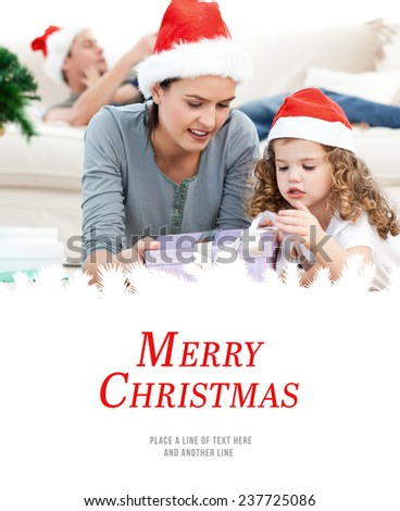 Mother and daughter unwrapping a present lying on the floor against merry christmas - stock photo
