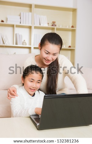 mother and daughter using a laptop at home