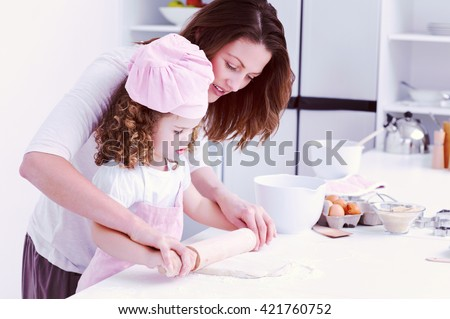 Mother and daughter using a rolling pin together in the kitchen - stock photo