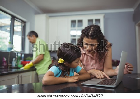 Mother and daughter using laptop in kitchen at home