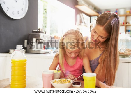 Mother And Daughter Using Mobile Phone At Breakfast Table - stock photo