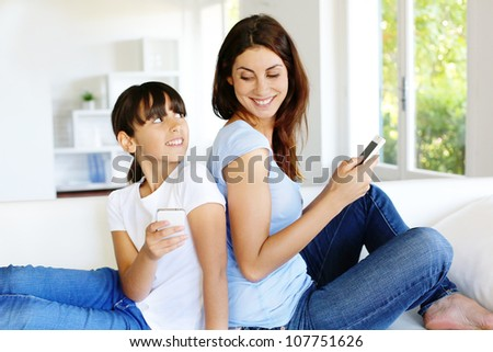 Mother and daughter using mobile phone at home - stock photo