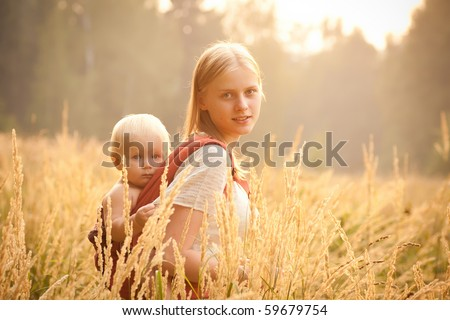 mother and daughter walking near forest by the road in the wheat field on sunset - stock photo