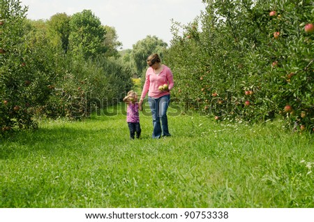 mother and daughter walking through a orchard