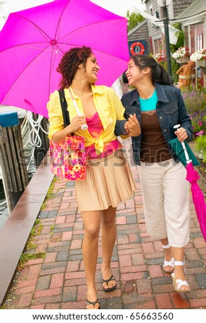 Mother and daughter walking with umbrella - stock photo