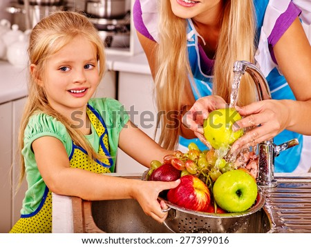Mother and daughter washing fruit at kitchen. Kid help. - stock photo
