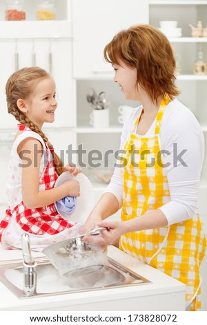 Mother and daughter washing the dishes together and talking - stock photo