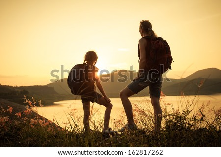 Mother and daughter  watching the sunset on the lake - stock photo