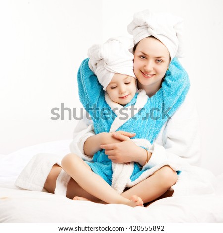 mother and daughter wearing bathrobes in bed at home - stock photo