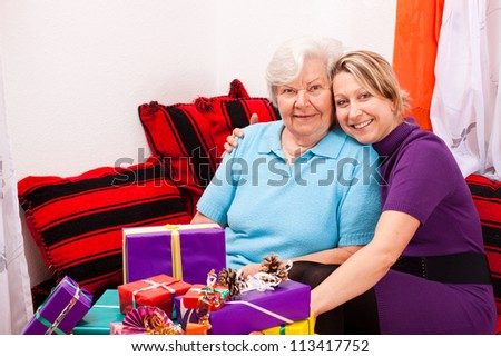 mother and daughter with a lot of presents on their couch
