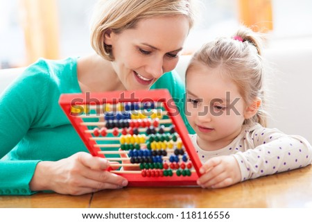 Mother and daughter with abacus - stock photo