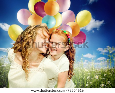 Mother and daughter with balloons - stock photo