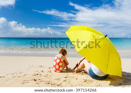 Mother and daughter with big yellow umbrella hiding from sun at tropical beach - stock photo