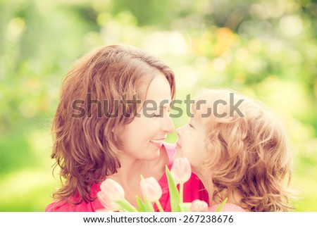 Mother and daughter with bouquet of flowers against green blurred background. Spring family holiday concept. Mother's day - stock photo