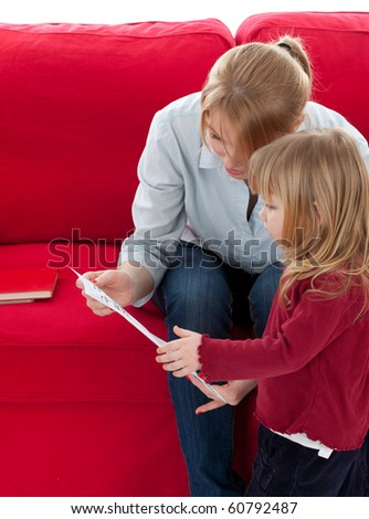 mother and daughter with curiosity looking at paper - stock photo