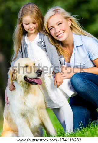 Mother and daughter with dog sitting on the grass at the summer park - stock photo