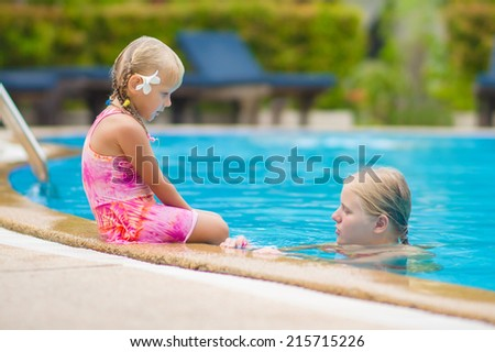 Mother and daughter with flower behind ear have fun at pool side in tropical beach resort - stock photo