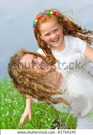 Mother and daughter with flower. Focus on eyes - stock photo