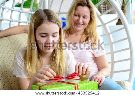 mother and daughter with green gift box in a chair - stock photo