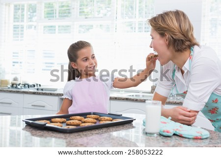 Mother and daughter with hot fresh cookies at home in kitchen - stock photo
