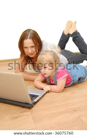 Mother and daughter with laptop on wooden  floor - stock photo