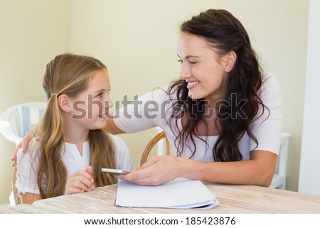 Mother and daughter with mobile phone looking at each other in house - stock photo