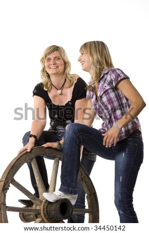 Mother and daughter with old car-wheel - stock photo