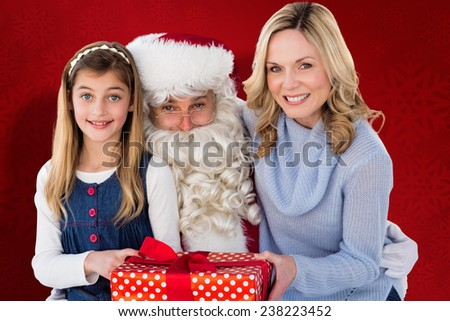 Mother and daughter with santa claus against red snowflake background