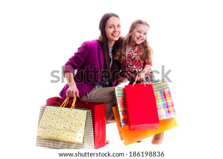 mother and daughter with shopping bags, isolated on white background - stock photo