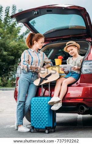 mother and daughter with suitcases in car trunk using tablet
