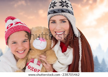 Mother and daughter with teddy against blurred fir tree forest - stock photo