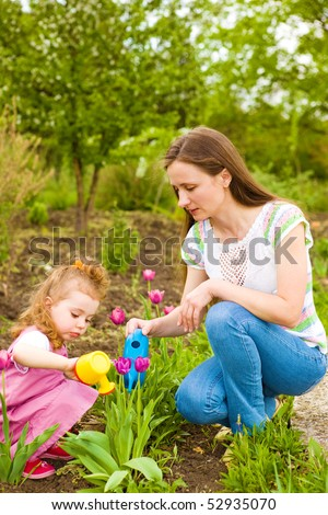 Mother and daughter working  in the garden - stock photo