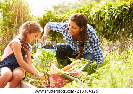 Mother And Daughter Working On Allotment Together - stock photo