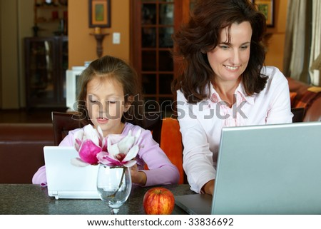 mother and  daughter working on laptops on a home background