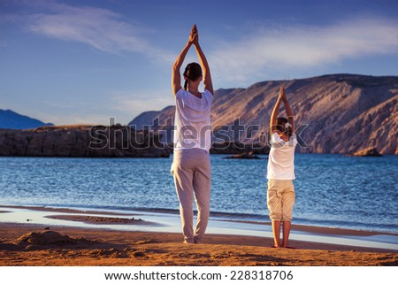 Mother and daughter, yoga on the beach early in the morning - stock photo