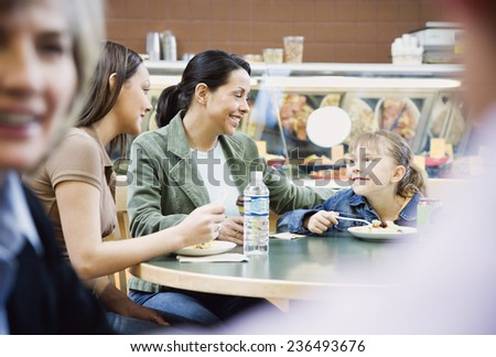 Mother and Daughters Eating at Supermarket Deli - stock photo