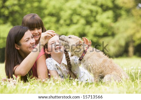 Mother and daughters in park with dog smiling - stock photo