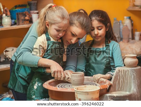 mother and daughters mold with clay, pottery children - stock photo