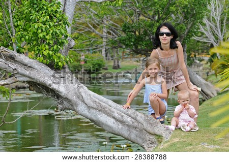 Mother and daughters near the river - stock photo