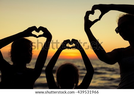 Mother and daughters playing on the beach at the sunset time. Concept of happy friendly family. - stock photo