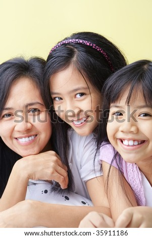 Mother and daughters posing together on bed - stock photo