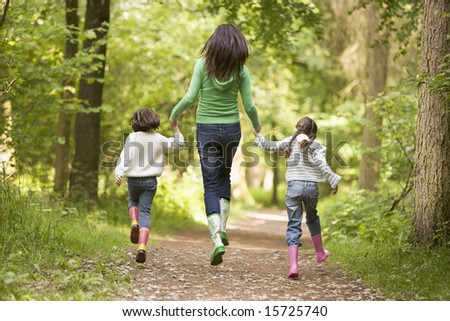 Mother and daughters skipping on path smiling - stock photo
